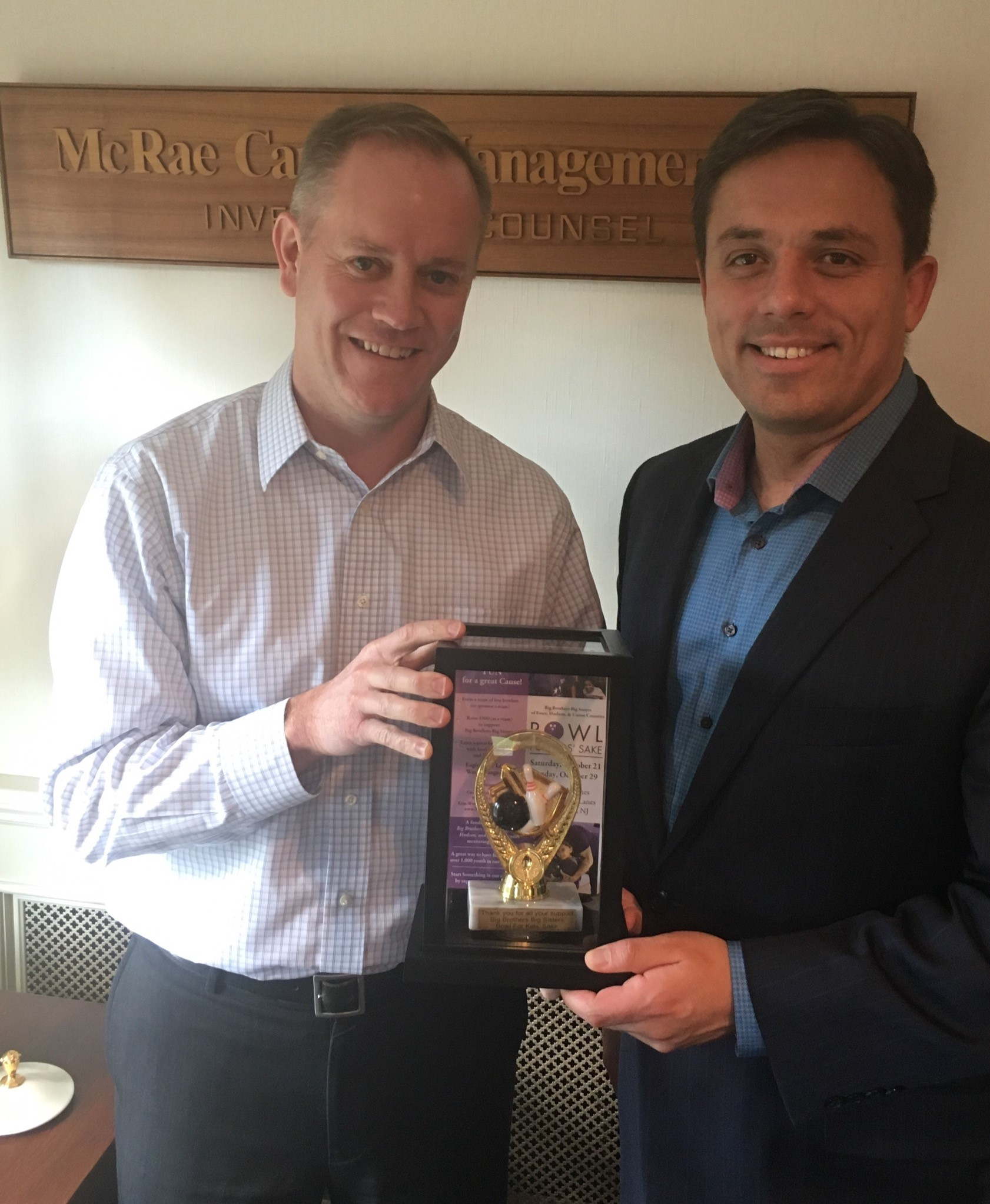 Peter McRae of McRae Capital Management is given a bowling trophy by BBBS regional CEO Carlos Lejnieks to recognize McRae's longtime support of Big Brothers Big Sisters of New Jersey (BBBS) at the Bowl For Kids Sake (BFKS) event in 2017.